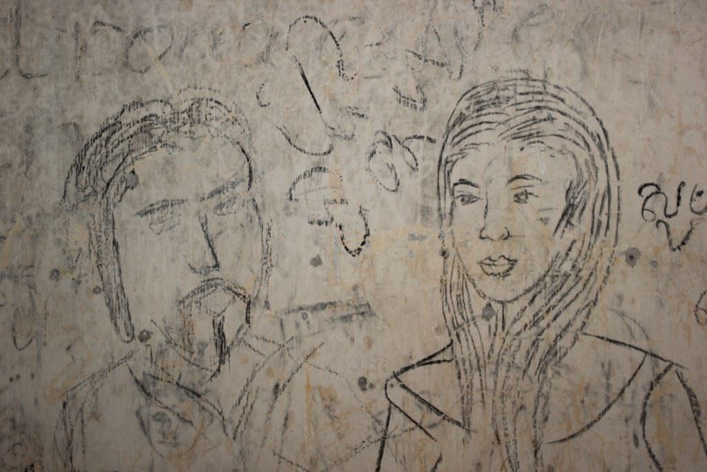 Drawing of a man and woman on the wall of an abandoned church.