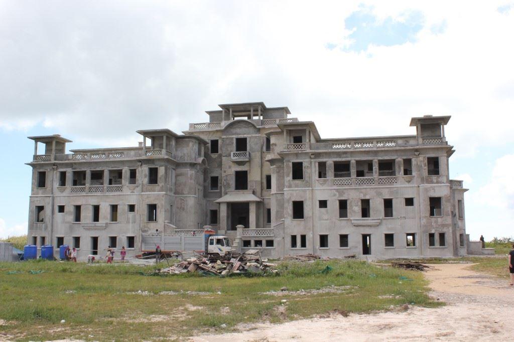 Large abandoned hotel on mountaintop.